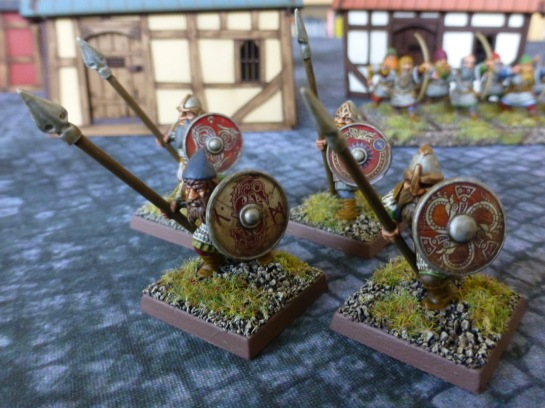 Four dwarfs with colourful decorated shields and spears