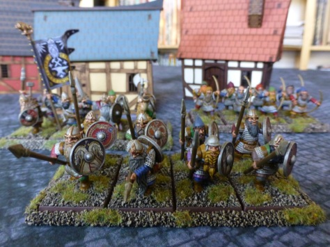 Three regiments of dwarfs in front of medieval timber frame buildings