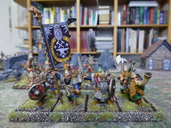 Two ranks of dwarfs in chainmail with shields and flying a banner