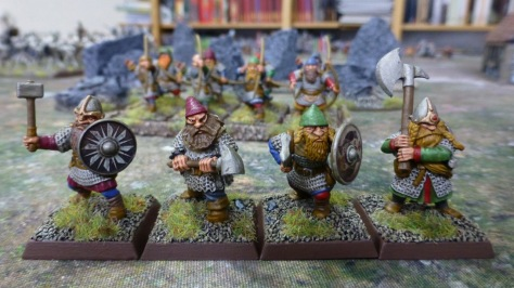 Four dwarfs wielding hammers and axes with one or both hands