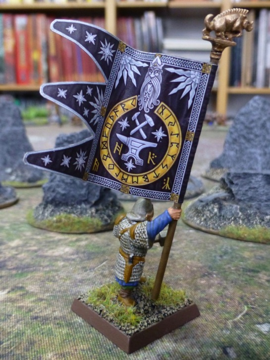A dwarf carrying a large banner depicting an anvil and crossed hammers