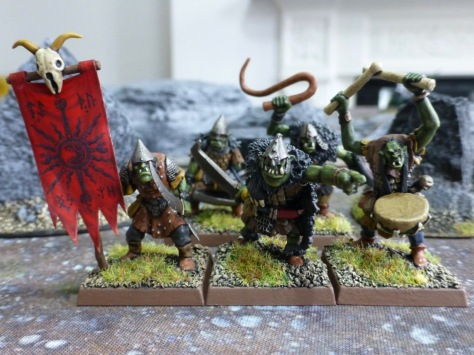 Group of five goblins including a standard bearer with red banner and a musician with drums