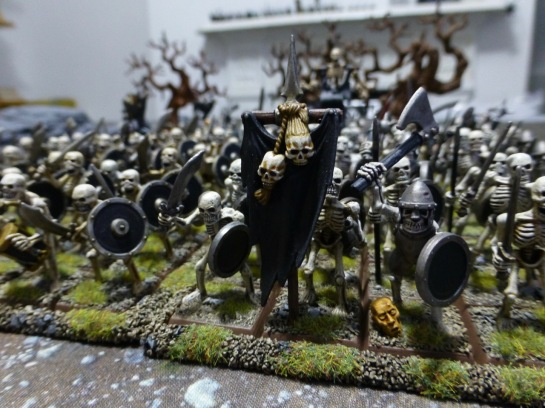 Close up view of skeleton warriors marching under a black banner hung with skull trophies
