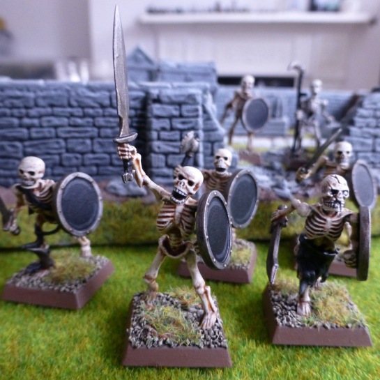 Skeletons with swords and shields emerging from a walled graveyard