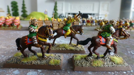 Side view of three Persian horse archers in colourful tunics and trousers