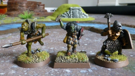 Three orc miniatures from different manufacturers lined up