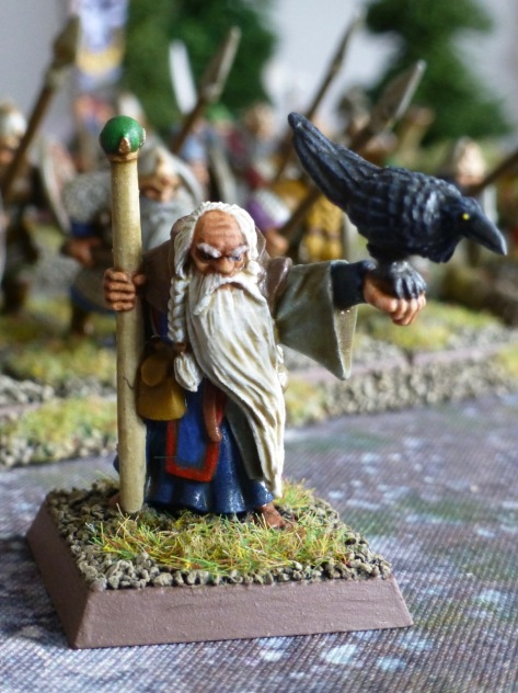 Dwarf wizard with a white beard carrying a staff and holding a raven on his outstretched arm