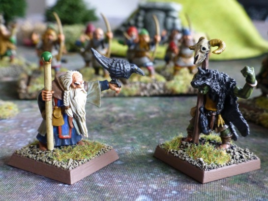 Dwarf wizard with a raven facing goblin shaman wearing a wolf pelt