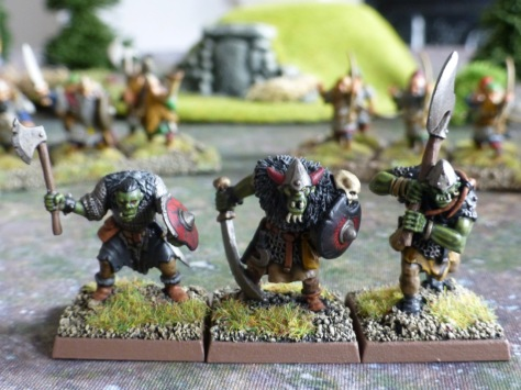 Three goblins with hand weapons, shields and a large axe