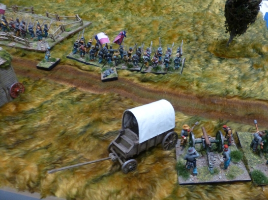 Cannon emplaced next to a wagon covering advancing infantry