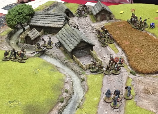 Groups of dark age warriors fighting through a hamlet
