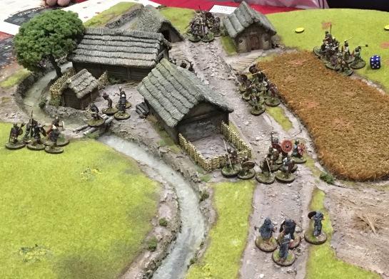 Groups of dark age warriors fighting through a hamlet