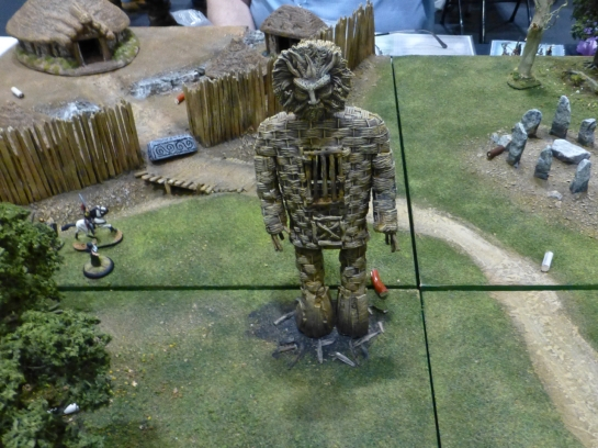Large wicker man in front of a wooden village