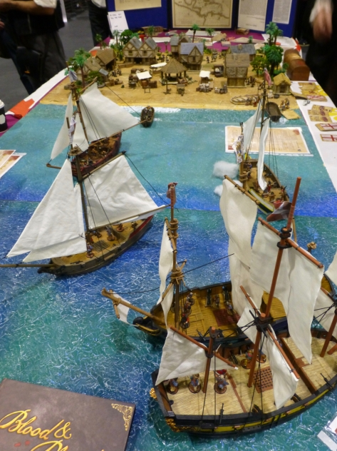 Five sailing ships close to a beach with a rustic settlement