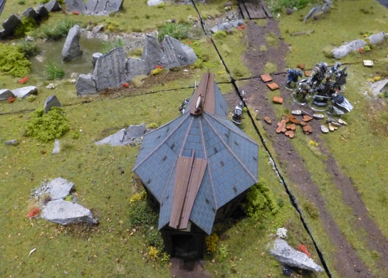 Top down view of a small temple set in grassland with a group of fighters passing by