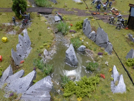A druidic stone circle with skirmishing warriors in the background