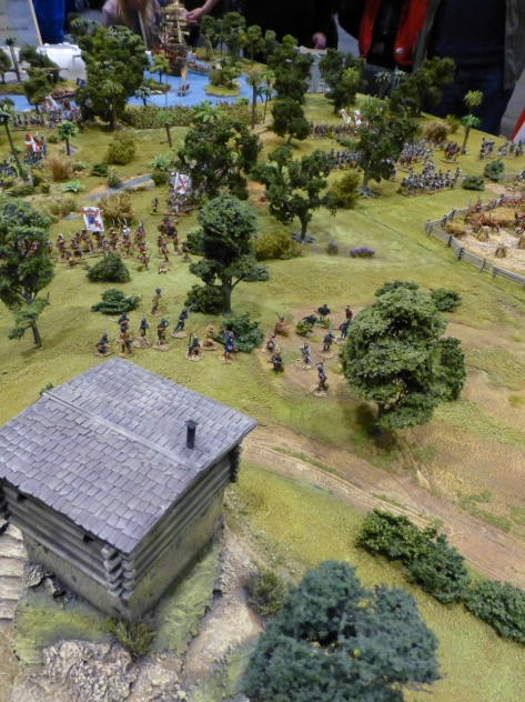 View from behind a watchtower over open woodland with scattered troops