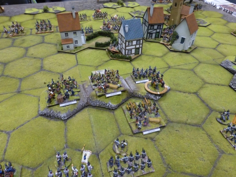 Units of soldiers on hex terrain surrounding a small town