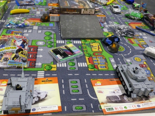 Toy floor play mat scattered with games boxes and plastic brick tanks