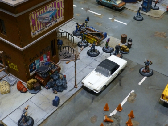 Street scene with piles of garbage, some cars and groups of gang members
