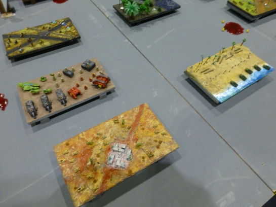 Close up of miniature gaming tables with desert and beach settings populated by tiny tanks and troops