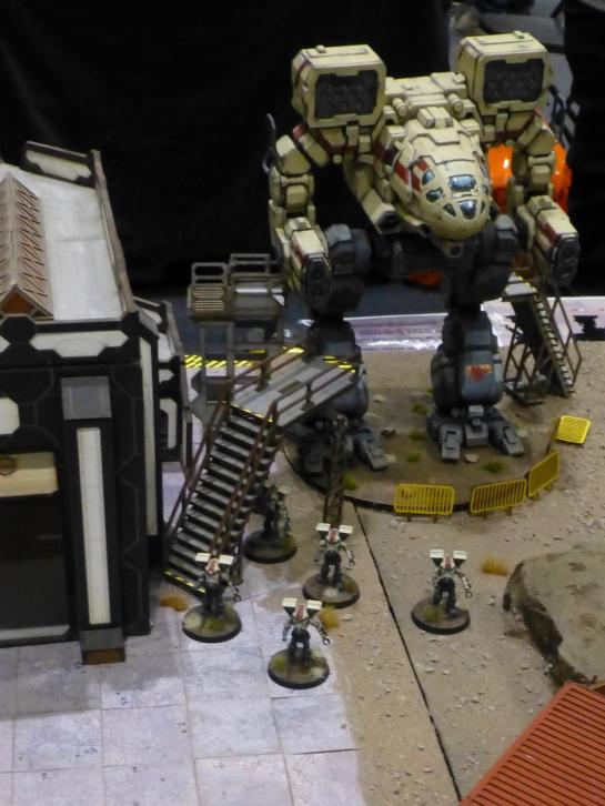 Battle mech standing next to a hangar building