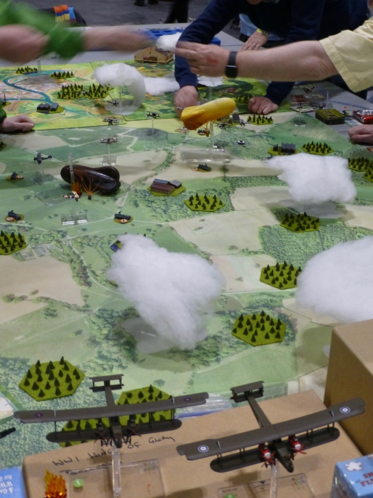 Aerial view of a battlefield with planes and air defence balloons amongst clouds