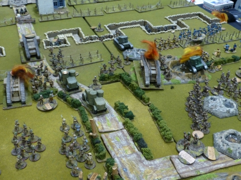 Tanks and infantry advancing onto trenches and barbed wire lines