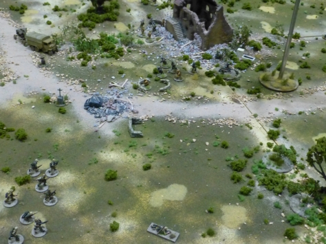 Infantry advancing over rough ground with scattered bombed out buildings