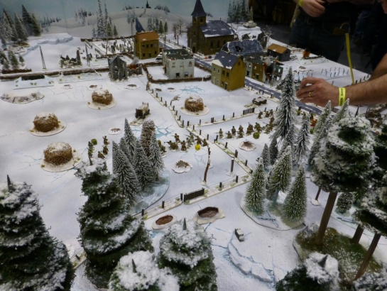 View over a snow covered forest towards a small town