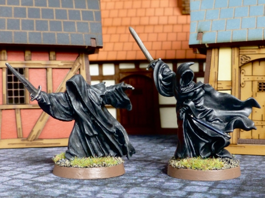 Two black cloaked figures with swords amongst medieval buildings