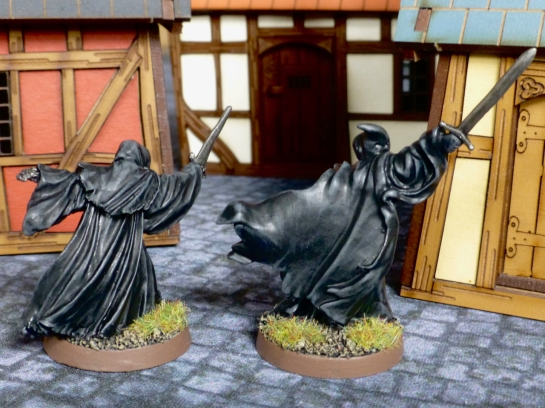 Two figures with black flowing robes from behind