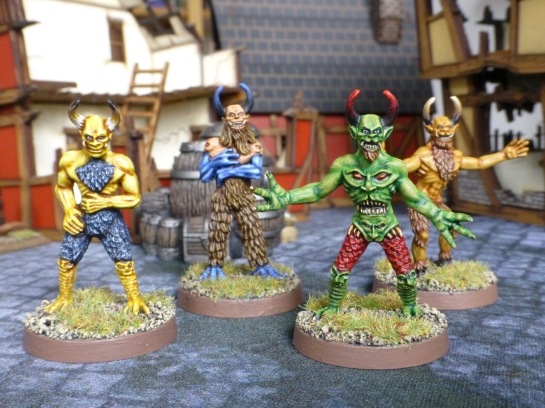 Four humanoid figures with horned heads and colourful skin in front of medieval buildings