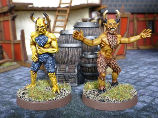 Two devil like figures with yellow and brown skin and fur