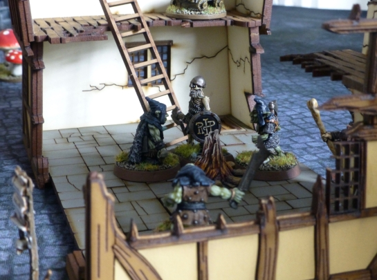 A timber framed house ruin with goblins and a skeleton fighting inside