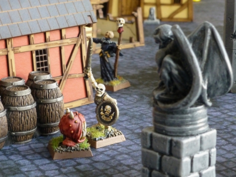 A stone gargoyle looking down on a fight between a skeleton and a red ball shaped creature