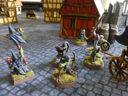 Goblins with bows taking aim at a skeleton warrior