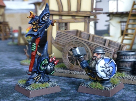 Goblin in black robes wielding a staff facing off against Dwarf with shield and hammer