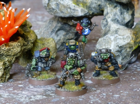 Four Orks in military gear with guns amongst rocky outcrops