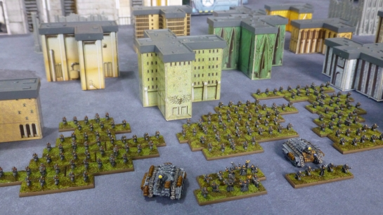 View from above over ranks of soldiers and two tanks in-between high rise buildings