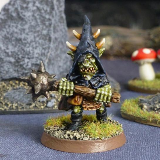 Goblin in a dark blue hood holding a double handed mace