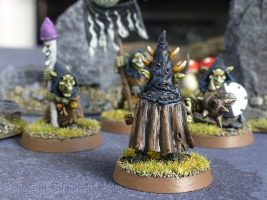 Back view of goblin leader wearing a brown tattered cloak