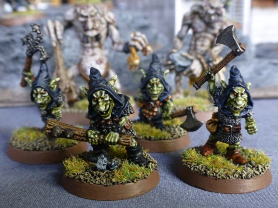 Four goblins wearing black hoods in front of two looming trolls
