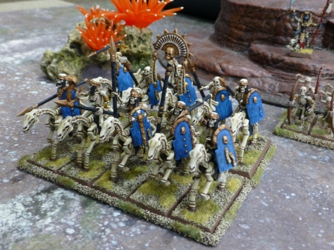 View from above on skeleton cavalry carrying blue shields and led by a banner bearer