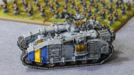 Large grey tank with a battle cannon in the main turret and side sponsons carrying lascannons
