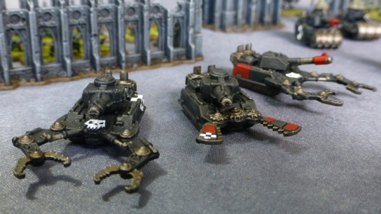 Three black tanks with claw and pincer attachments at the front