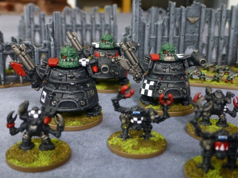 Black armoured war walkers of different sizes among building ruins