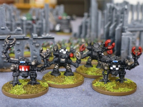 Four bipedal armoured walkers with guns and clawed arms
