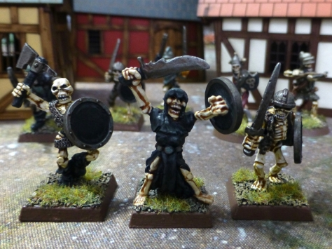 Three armed skeletons in a medieval town setting