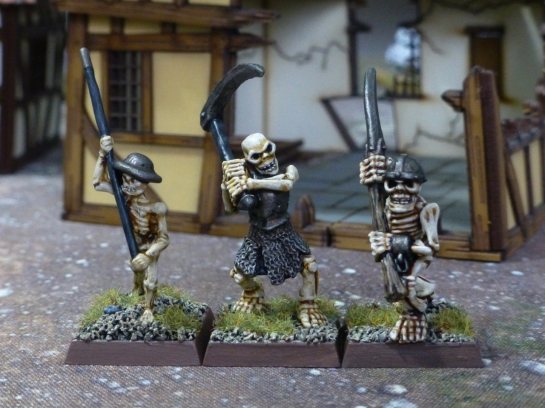 Three skeletons wielding scythes and other polearms